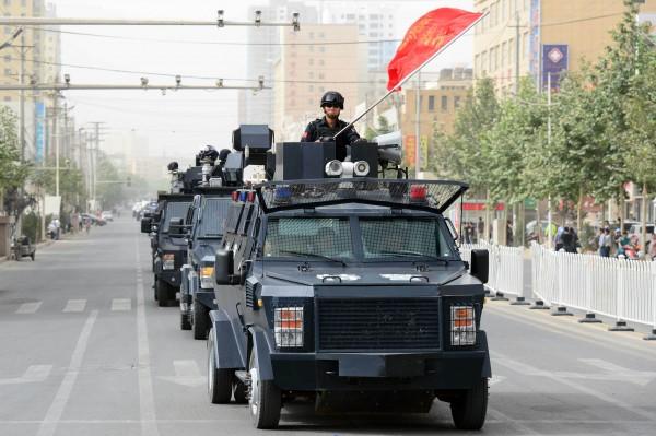 中國解放軍安全部隊在新疆大街行軍展示武力。盡其中國當局以反恐為由加強在新疆地區的維安力道,並因為官員強掀婦女頭罩引發死亡衝突。(法新社資料照)