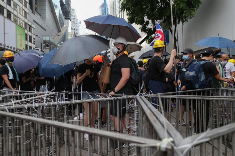 警方防線對面的示威者,以雨傘和鐵馬構築防線。(歐新社)