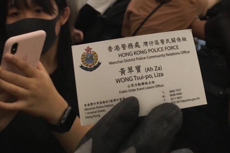 示威者在謊稱記者的男子身上發現香港警務處公眾活動聯絡主任的名片。(圖擷取自TG_反送中已核實資訊頻道)