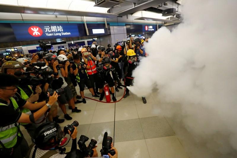 元朗地鐵站內有人手持滅火器噴射、以垃圾桶等雜物做出防線,和站口的警方對峙。(路透)