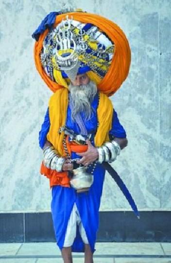 莫尼總是包著45公斤重的橙色大頭巾,並稱「如果不戴頭巾,就覺得自己不完整,總是害怕跌倒。」(圖擷取自中新網)