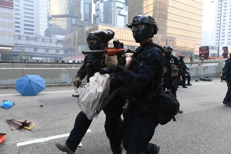 港警隨後將示威者拉起,把人頂在身體前方,並且槍口朝前。(法新社)