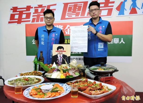 國民黨台中市長參選人盧秀燕發言人蔣豐懋(右)直播海陸大餐,桌上卻有林佳龍照片。(記者張菁雅攝)