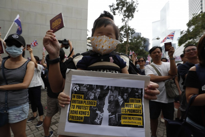 有些人高舉標語,指責中國違反「中英聯合聲明」,並要求香港落實「真普選」。(歐新社)