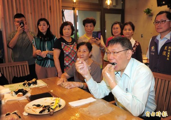 台北市長柯文哲(右)出席大安老人服務暨日間照顧中心開幕活動,柯文哲與長輩們一同做壽司。(記者王藝菘攝)