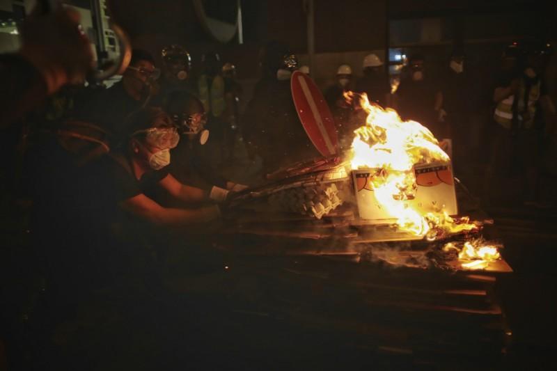 示威者點燃易燃物,試圖阻擋警方推進。(美聯社)
