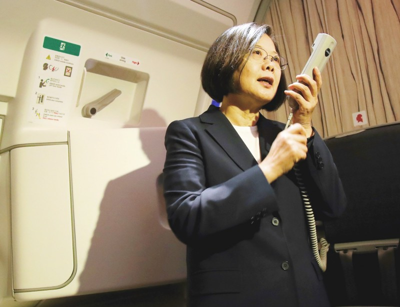 President Tsai Ing-wen speaks to passengers on a China Airlines airplane's tannoy system yesterday after takeoff on the first leg of a 12-day state visit to four Caribbean diplomatic allies.  Photo: CNA