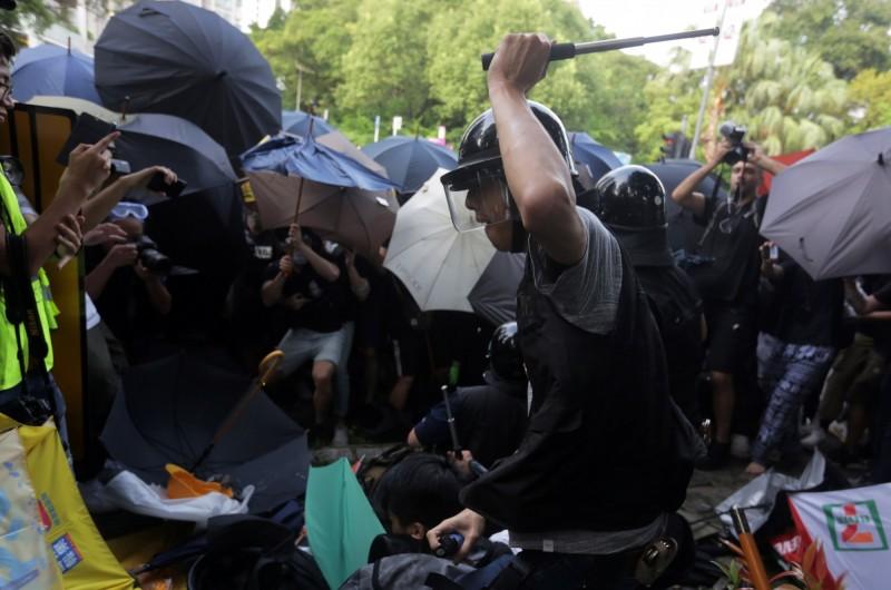 香港警察手持警棍抽打示威者。(歐新社)