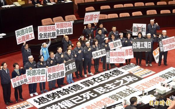 勞動基準法部分條文修正案」完成三讀,國民黨團立委高舉標語抗議。(記者羅沛德攝)