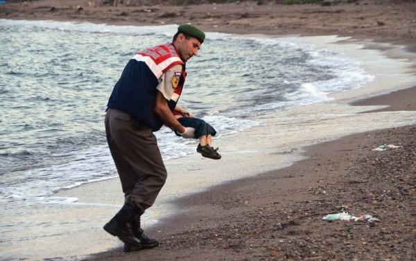 海巡人員將男童的屍體抱起。(圖擷自「法新社」)