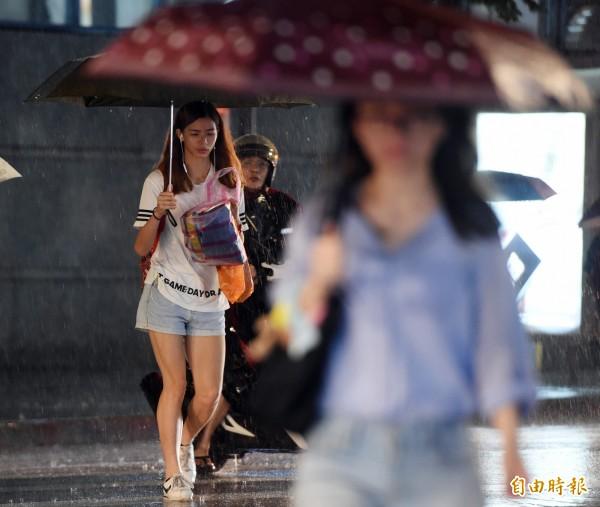 瑪莉亞颱風來襲,台北市區10日入夜後風雨漸增,行人紛紛以雨具遮擋風雨。(記者廖振輝攝)