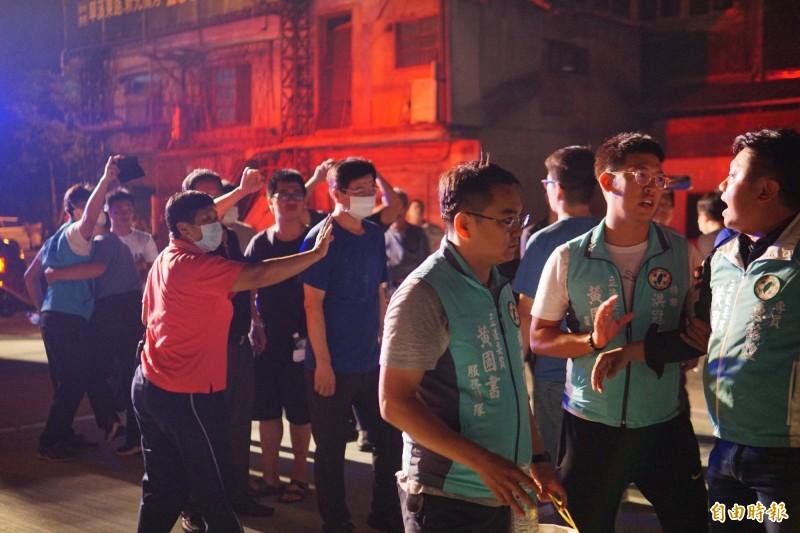 國民黨市議員羅廷瑋(左一持手機者)和立委黃國書的專員惠銘煌(右一),今天凌晨在新民街火場爆發衝突,旁人連忙隔開勸阻。(記者何宗翰攝)