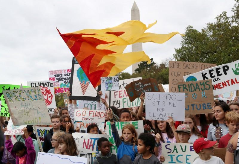 許多學生聚集在白宮外高舉標語,參與青年氣候運動。(路透)