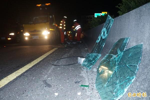 客運疑為閃避前方自小客車,不慎擦撞內側護欄,玻璃碎裂一地。(記者黃佳琳攝)