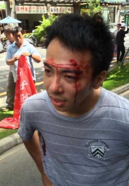 一名莊姓男子欲阻擋張的車隊,警方見狀立馬拉開,還疑似對莊男頭部著地過肩摔。(圖擷取自基進側翼臉書)