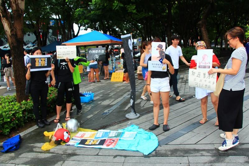 由在台香港青年組成的團體「香港邊城青年」17日原定在台中市市民廣場發起野餐交流活動,但因午後大雨,活動臨時改為在草悟道旁人行道快閃擺攤,多名在台港人現場高舉標語、看板表達訴求。(中央社)