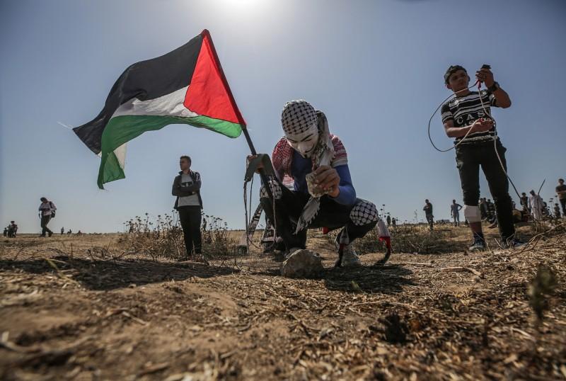 然美國從去年開始降低聯合國提供給巴勒斯坦難民的金援,造成了6000萬美金(約新台幣18.8億)的缺口,因此聯合國呼籲世界各國提供經濟援助。圖為帶著巴勒斯坦國旗的加薩走廊人民,抗議戰爭帶來的災害。(歐新社)
