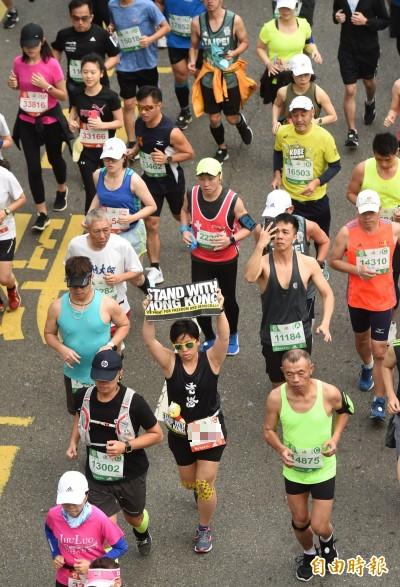 2019台北馬拉松15日舉行,共有2萬8千名選手共襄盛舉,跑者中也可看到參賽者高舉挺港標語。(記者方賓照攝)