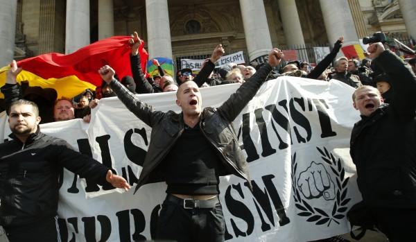 示威者拉布條高呼民族主義口號、反對移民,高呼「這是我們的家」。(美聯社)