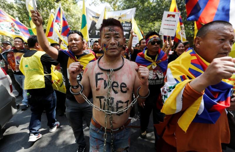 西藏流亡政府的支持者,身戴枷鎖,在胸口寫上「Free Tibet」的字樣在街頭遊行。(路透)