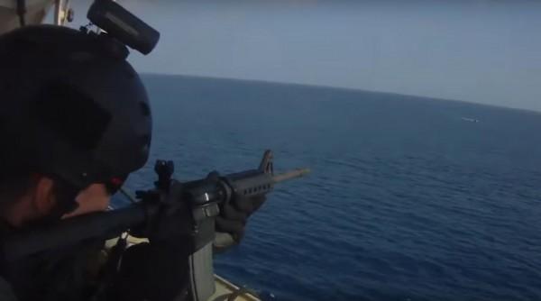 貨輪上的安保人員持槍瞄準遠方的海盜快艇。(圖擷自YouTube)