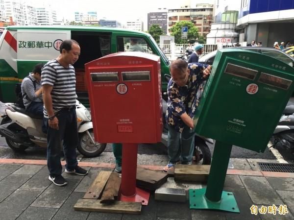 中華郵政人員在現場檢視,要把郵筒再歪回來。(記者林煙婷攝)