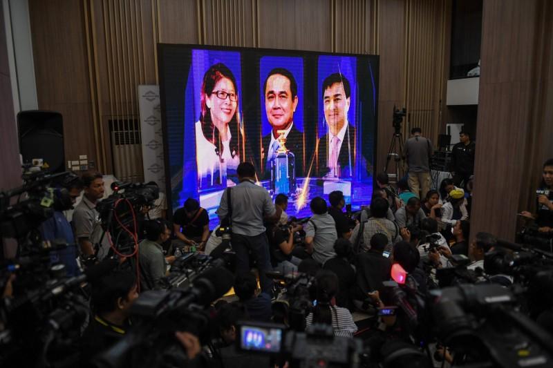 泰國週日(24日)舉行國會大選,目前正陸續開票、計票,軍政府總理帕拉育(螢幕畫面中間者)有機會繼續掌權。(法新社)