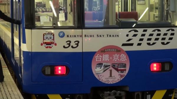 車頭前方掛上一面印有京急電車和台鐵太魯閣號的圓形紀念牌。(圖片擷取自YouTube)