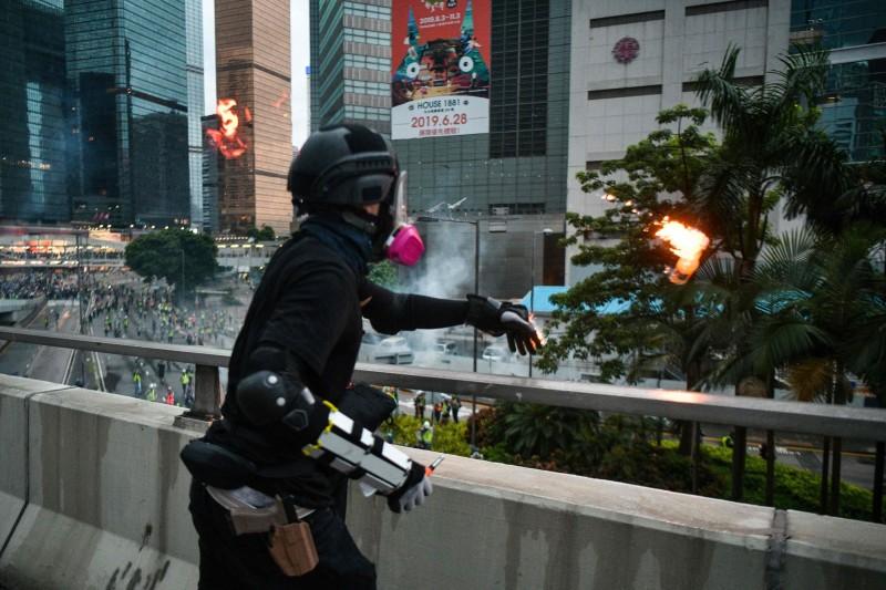 香港網友揭發,該名丟擲汽油彈的示威者疑似是由港警假扮。(法新社)