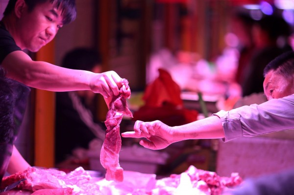 中國民眾在攤販購買豬肉,圖僅為示意。(路透)