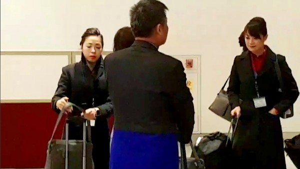 A video image released by Japanese customs shows a China Airlines flight attendant, surnamed Kuan, left, taking her carry-on luggage through customs on arrival in Osaka on Saturday. Photo copied by Tony Yao, Taipei Times