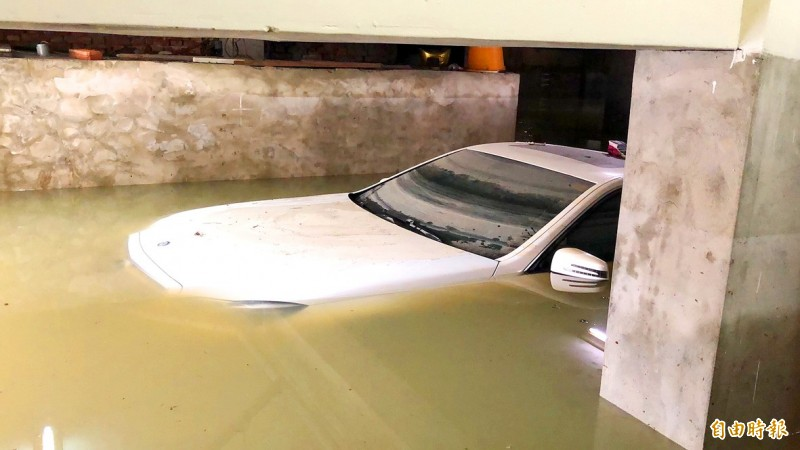 A car purchased two months ago is submerged in floodwater in Tainan yesterday. Photo: Wang Chieh, Taipei Times