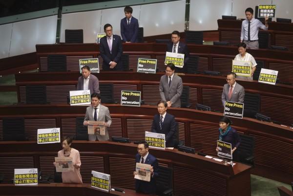 泛民派議員們在林鄭月娥要上台報告前,全體起立並高舉「捍衛新聞自由」、「停止打壓記者」等標語,呼喊著口號抗議。(美聯社)