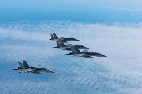 日本自衛隊戰鬥機去年緊急升空904次,其中約有55%都是針對中國。圖為日本自衛隊兩架F-15與美軍兩架F/A-18演訓。(路透)