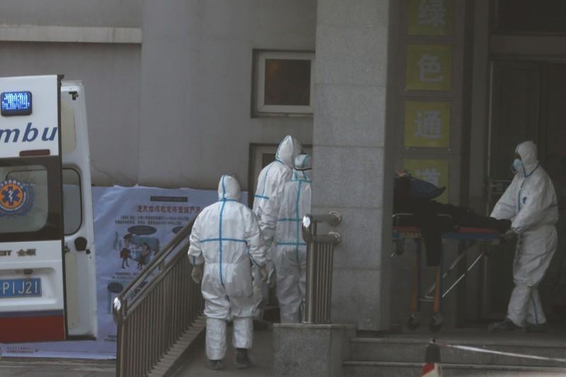 中國醫護人員,正在轉移武漢肺炎患者。(路透)