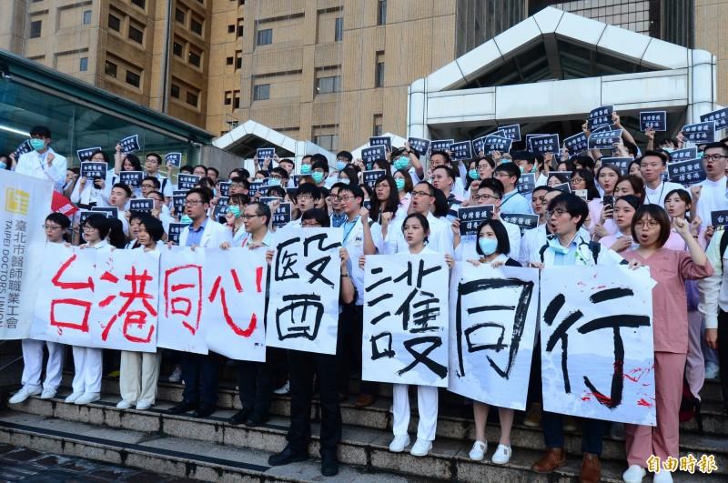 台灣醫護撐香港,上百名台灣醫護人員在台大醫院正門外階梯處,一同呼喊「台港同心,醫護同心」口號。(記者王藝菘攝)
