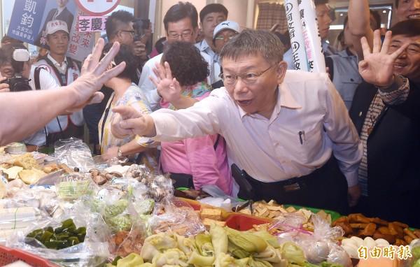 台北市長柯文哲前往木新市場掃街,和攤商、民眾拜票,一名攤商熱情比出4號手勢,柯文哲卻指著攤商受傷的大拇指表達關切。(記者廖振輝攝)