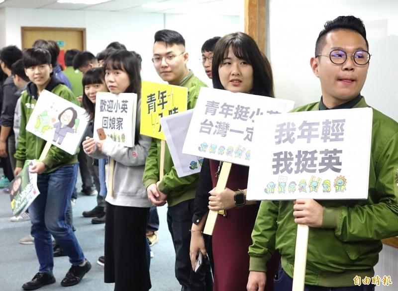 民進黨年輕黨工拿著看板,歡迎總統蔡英文回娘家。(記者王藝菘攝)