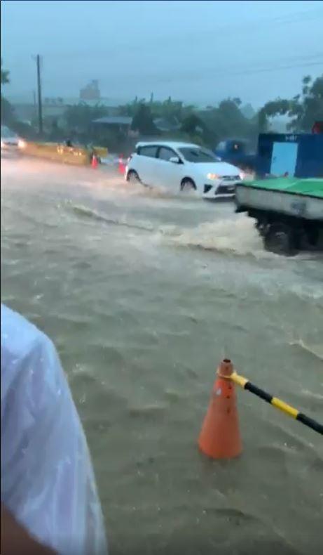 一名高雄韓粉「仁武阿鴻」特地在大雨中開車,檢視各處淹水情形,其中他一度站在黃濁色的泥水中強調「這是積水,不是淹水」。(圖擷取自臉書)