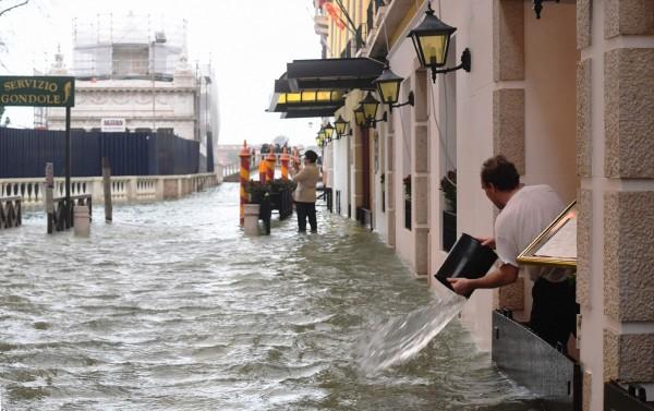 民眾將淹入屋內的水舀出。(法新社)