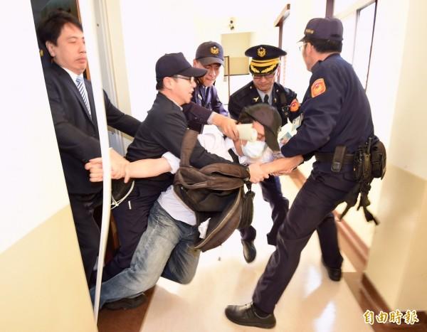 警察隨後將抗議者拉出會議室。(記者羅沛德攝)