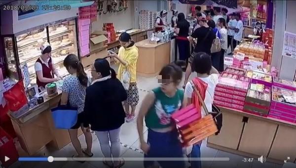 一名綠衣女子趁店員忙於應付客人時,手腳俐落的抱了6盒禮盒轉身就往店外走。(圖擷取自爆料公社)