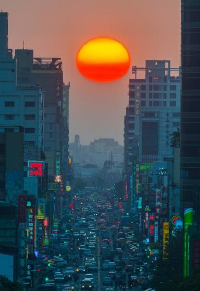 名列紐約奇景之一的「曼哈頓懸日」,在高雄也看得到,今天的日落恰好落在高雄的高樓之間,許多高雄的民眾在黃昏時,也都觀看到這個令人喜悅的美景。(記者張忠義攝)