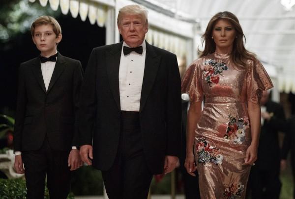 川普夫人梅蘭妮亞(右)、小兒子拜倫(左)出席此次跨年派對,但川普(中)本人並未出席。(美聯社)