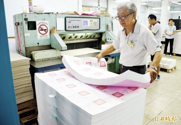 A worker stacks newly printed referendum ballots yesterday in Pingtung County. Photo: Hou Cheng-hsu, Taipei Times