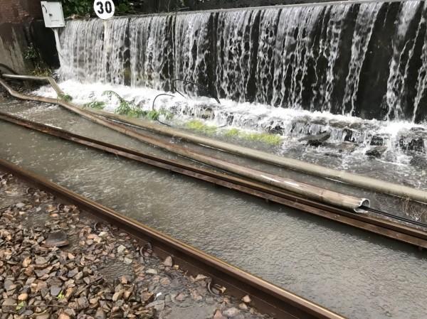 大雨侵襲,鳳山站南端一度因水淹軌面不通,目前東線須減速慢行。(圖:台鐵局提供)