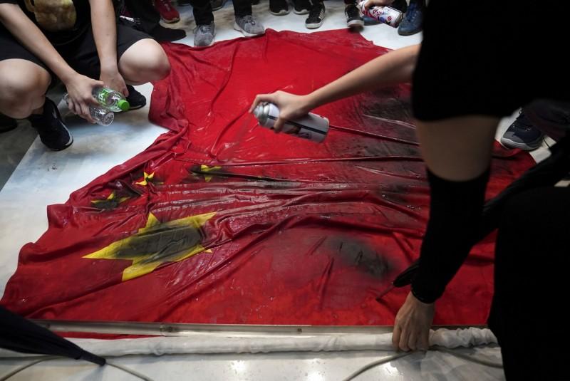 示威者在中國五星旗上噴漆。(路透)