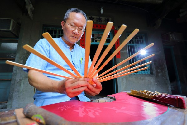 施政均身為鹿港東華扇廠第2代傳人,從小接觸製扇已有近50年時間。(記者李惠洲攝)