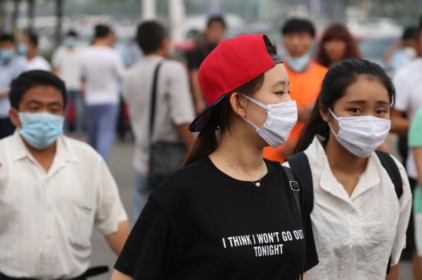 民眾也紛紛戴上口罩。不過英國專家表示,最好盡快離開附近區域,如果非進入爆炸區域也要戴上全罩式口罩,一般口罩「擋不住」。(法新社)