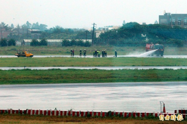 機場公司出動消防水車清理跑道上胎皮碎屑。(資料照,記者朱沛雄攝)